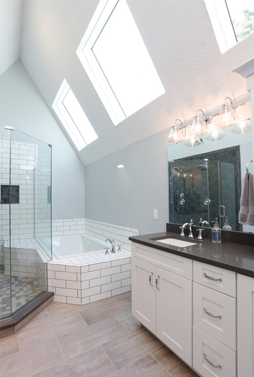 Beautifully renovated bathroom featuring shower and soaking tub with skylights overhead