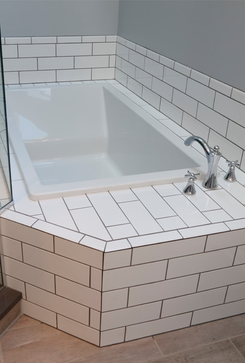 Slim soaking tub with subway tile and grey grout