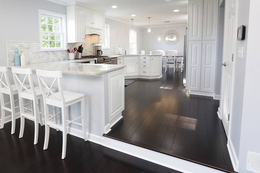 Kitchen with white cabinets and counters and dark wood flooring