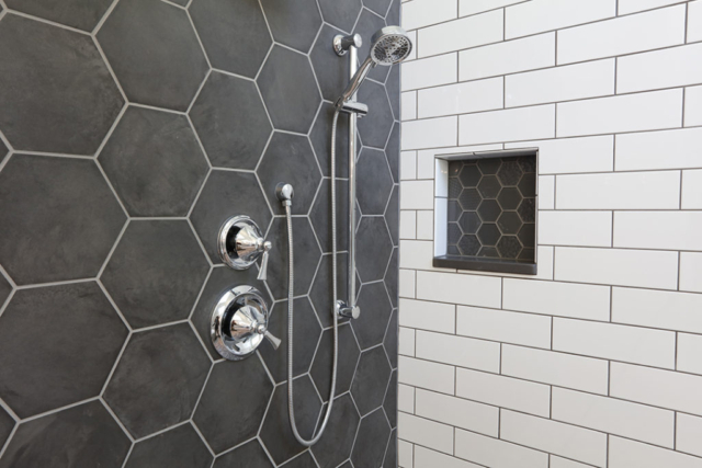 Custom shower enclosure with white and gray tiles, hexagon shapes and glass tile