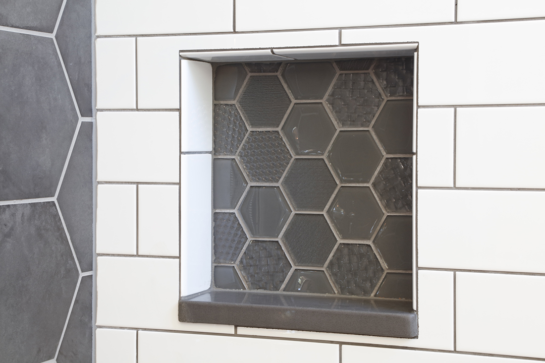 Built-in shelf in shower with hexagon glass tile