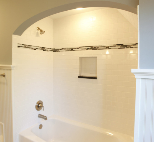 Bathtub surround with subway tile and contrasting accent tile