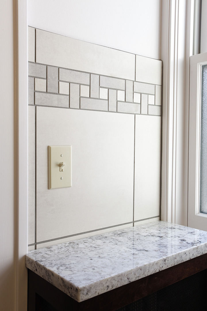 Wall tile in bathroom features accent tile inlay