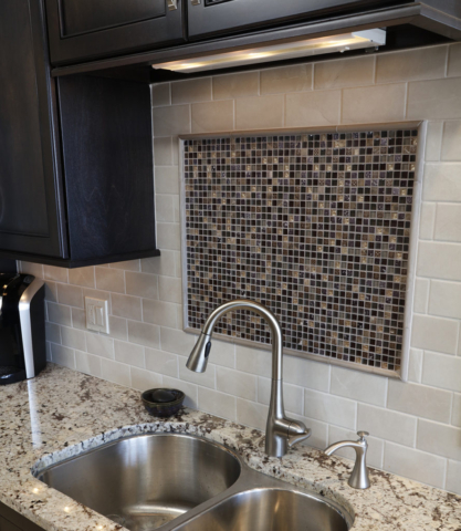 Kitchen backsplash with subway tile and decorative mosaic inlay focal point
