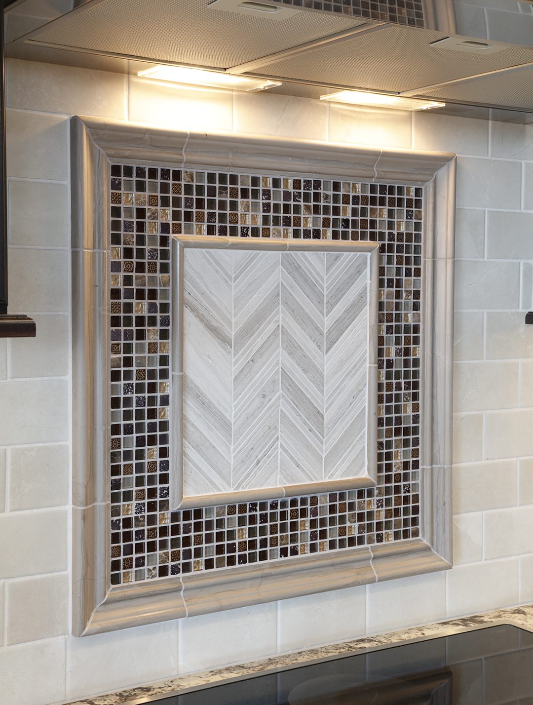 Tile inlay with decorative tiles creates dimension, interest in kitchen