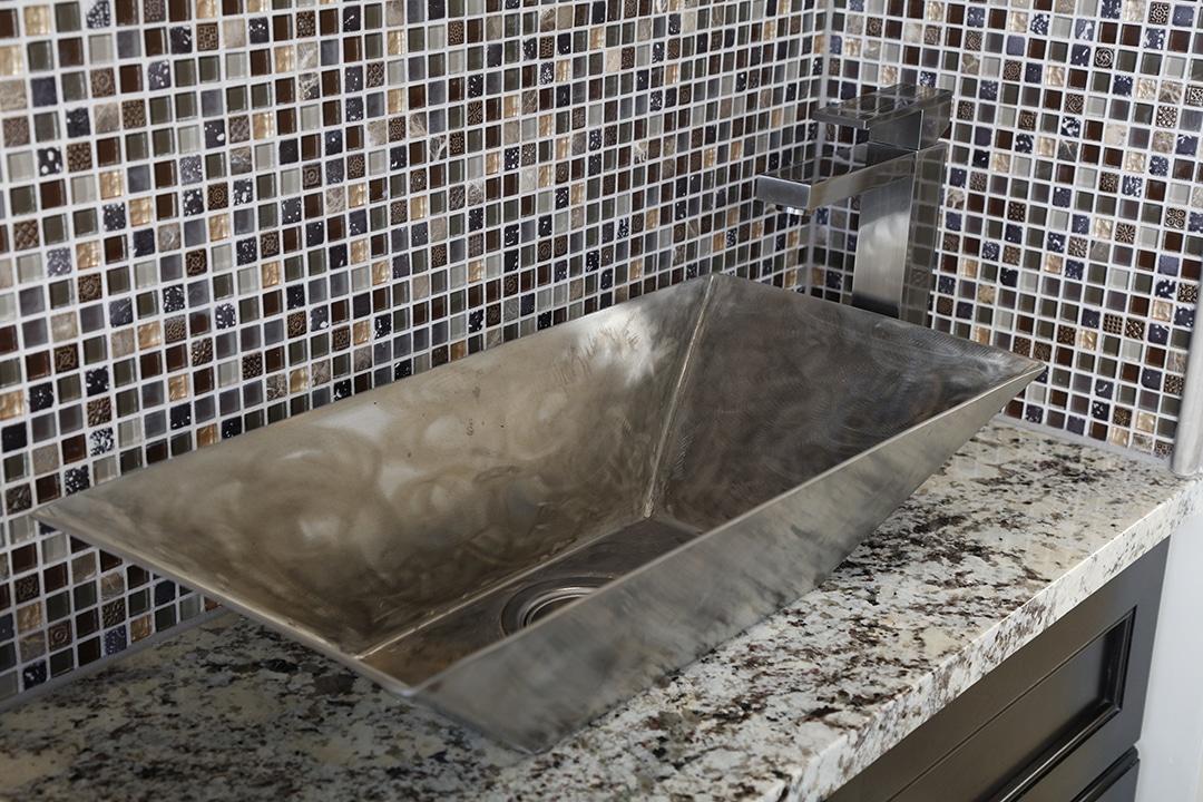 Wet bar with custom  metal vessel sink and glass mosaic tile backsplash